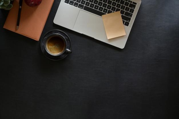 Laptop mit bürogerät auf dunklem ledernem desktop Premium Fotos