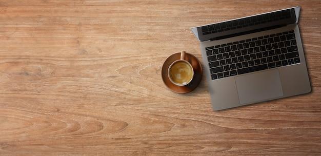 Laptop mit kaffee auf holztisch. panorama-banner Premium Fotos