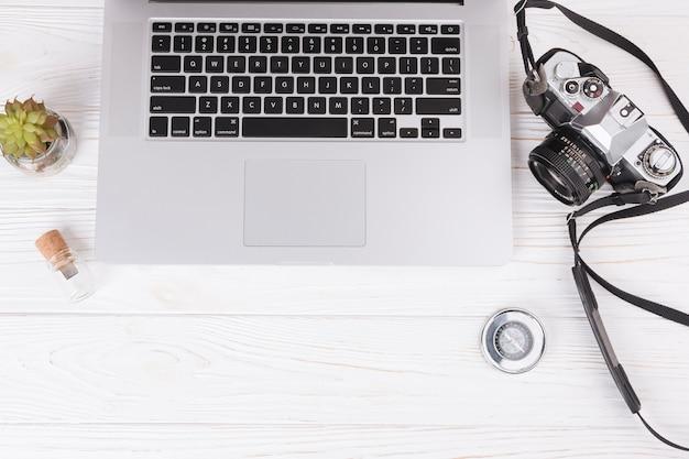 Laptop mit kamera und kompass auf dem tisch Kostenlose Fotos