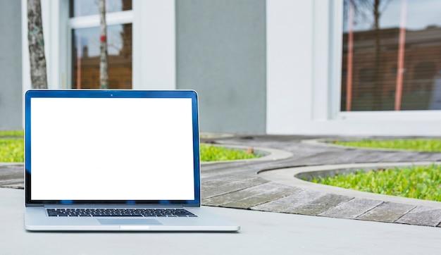 Laptop mit leerem bildschirm vor haus Kostenlose Fotos