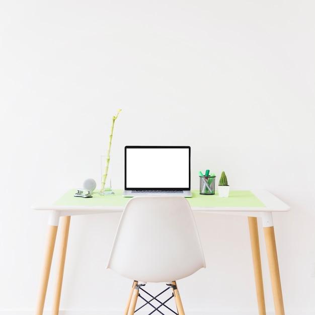 Laptop mit leerem weißem bildschirm auf schreibtisch vor wand Kostenlose Fotos