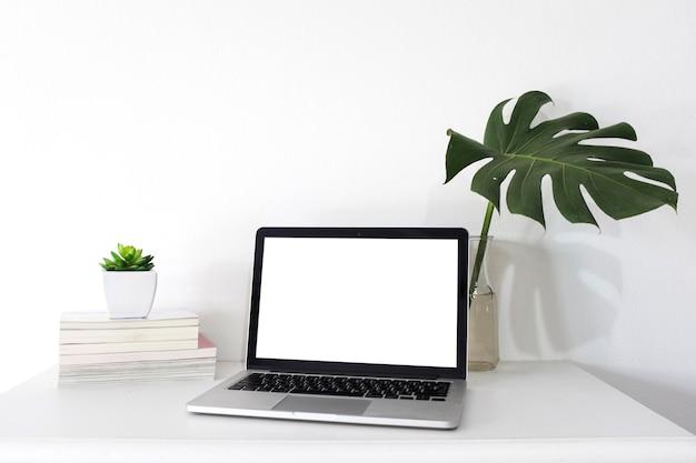 Laptop mit leeren weißen bildschirm auf schreibtisch Kostenlose Fotos