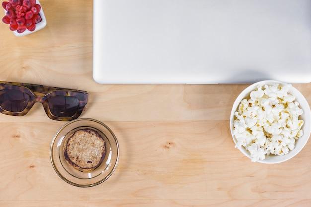 Laptop mit Popcorn und Sonnenbrillen auf dem Tisch Kostenlose Fotos