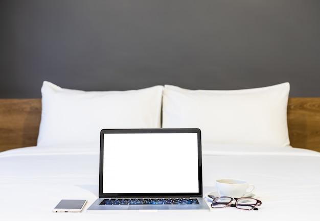 Laptop mit smartphone, kaffeetasse und brille auf dem bett Premium Fotos