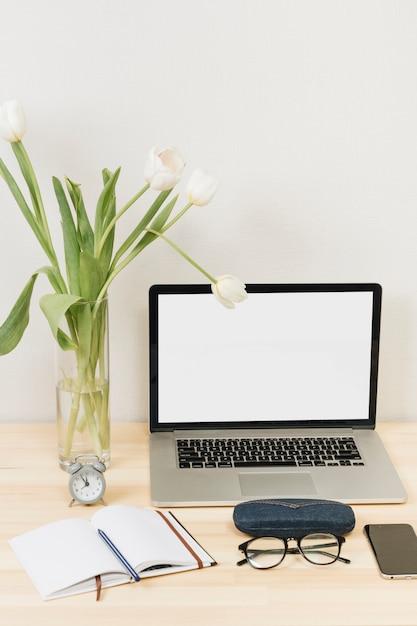 Laptop mit tulpen im vase auf holztisch Kostenlose Fotos