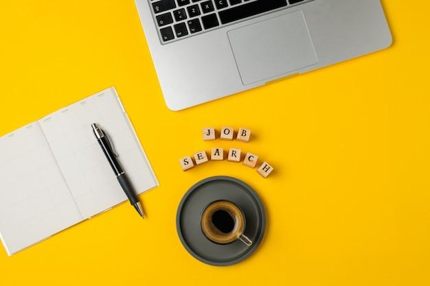 Laptop, notizblock, stift, kaffeetasse, smartphone auf hellem gelb Premium Fotos