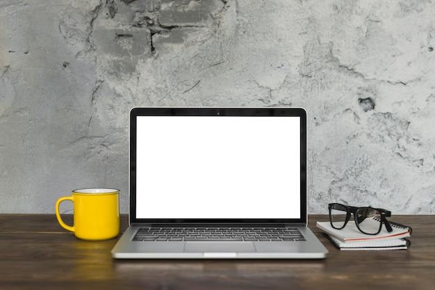 Laptop öffnen; gelbe kaffeetasse; schauspiel; und tagebuch auf holztisch mit hintergrund der verwitterten wand Kostenlose Fotos