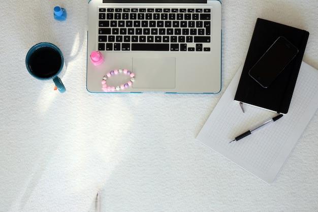 Laptop, smartphone, becher und nagellack Kostenlose Fotos