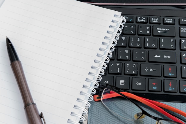Laptop, stift, notizblock und brille Premium Fotos