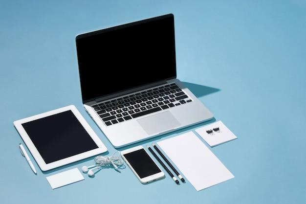 Laptop, stifte, telefon, notiz mit leerem bildschirm auf dem tisch Kostenlose Fotos