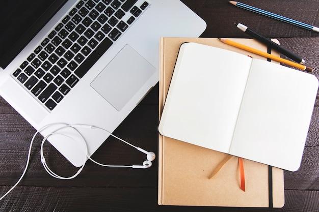 Laptop und kopfhörer nahe notizblöcken und bleistiften Kostenlose Fotos
