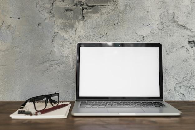 Laptop und schauspiel mit büromaterialien auf hölzernem schreibtisch mit alter wand Kostenlose Fotos