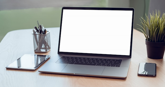Laptop und tablet, smartphone mit leerem bildschirm für ihre werbung auf dem tisch im büro. Premium Fotos