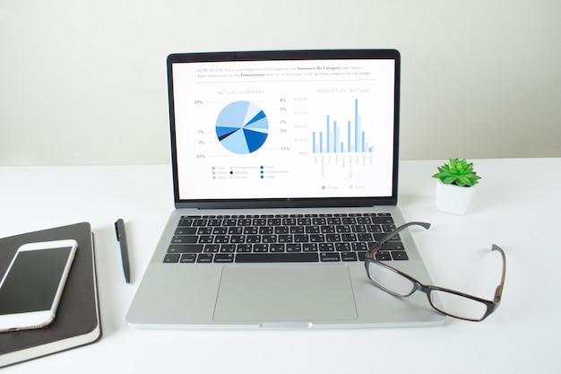 Laptopbildschirm, der finanzdiagrammanalyse, schreibtischschirm mit verschiedener ausrüstung von geschäftsmännern zeigt Premium Fotos