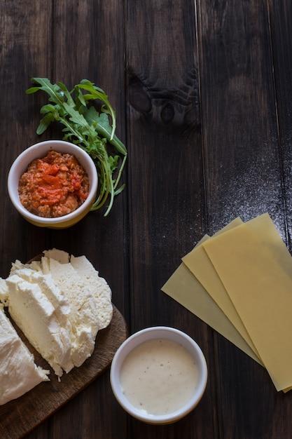 Lasagne backen. italienisches essen. roher lasagnenteig, mozzarella, soße aus bolognese Premium Fotos