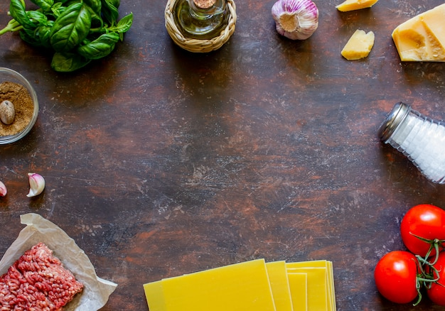 Lasagne, tomaten, hackfleisch und andere zutaten. dunkler hintergrund. italienische küche. Premium Fotos