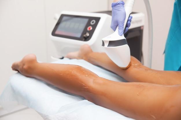 Laserepilation und kosmetologie im schönheitssalon. verfahren zur haarentfernung. konzept für laser-epilation, kosmetologie, spa und haarentfernung. schöne frau, die das haar entfernt auf fahrwerkbeinen erhält Premium Fotos