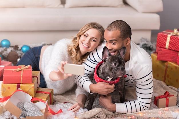 Lass uns ein selfie machen. gut aussehender glücklicher emotionaler mann, der seinen hund umarmt und während des handys lächelt Premium Fotos