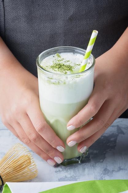 Latte aus matcha-grüntee. das barista-mädchen hält ein glas mit einem gesunden getränk in der hand. Premium Fotos