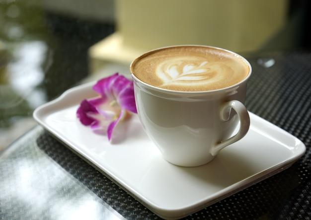 Latte nahaufnahme im weißen becher auf keramiktablett mit unscharfer plumeriablume. Premium Fotos