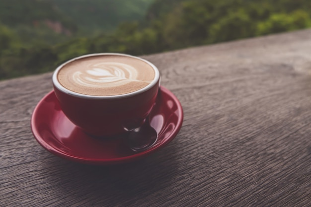 Lattekunst-kaffeetasse auf dem holztisch, ebenenlage Premium Fotos
