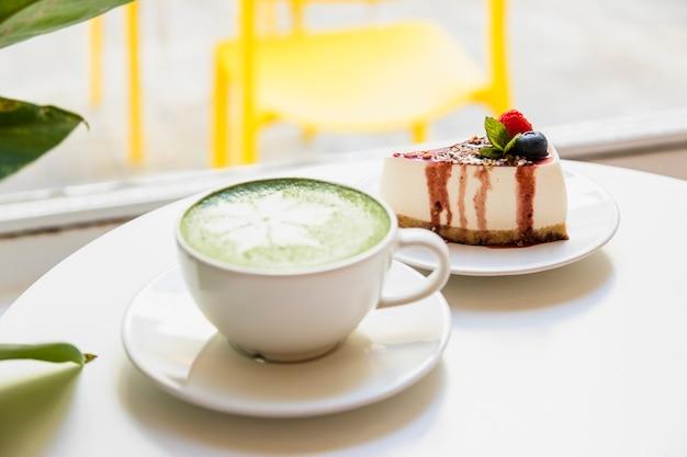 Lattekunst mit japanischem matcha und käsekuchen des grünen tees auf weißer tabelle Kostenlose Fotos