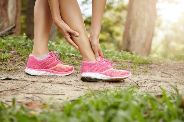 Laufen sportverletzung. sportlerin jogger trägt rosa turnschuhe und berührt ihren verdrehten oder verstauchten knöchel beim joggen oder laufen im freien. Kostenlose Fotos