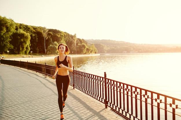 Laufende frau. läufer, der im sonnigen hellen licht rüttelt. vorbildliches training der weiblichen eignung draußen im park Kostenlose Fotos