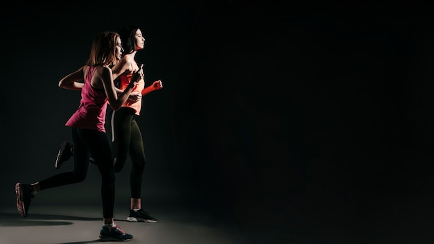 Laufende sportliche frauen in der dunkelheit Kostenlose Fotos