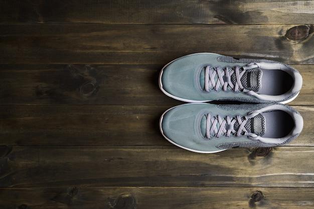 Laufende sportschuhe auf hölzerner hintergrund draufsicht mit kopienraum. Premium Fotos