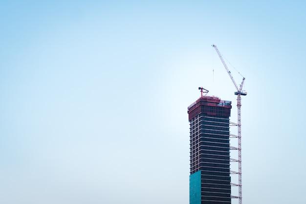 Laufender bau des wolkenkratzers in der modernen stadt mit hohen roten kränen, stahlrahmenstruktur und glaswand des außengebäudes mit klarem blauem himmel im hintergrund. Premium Fotos