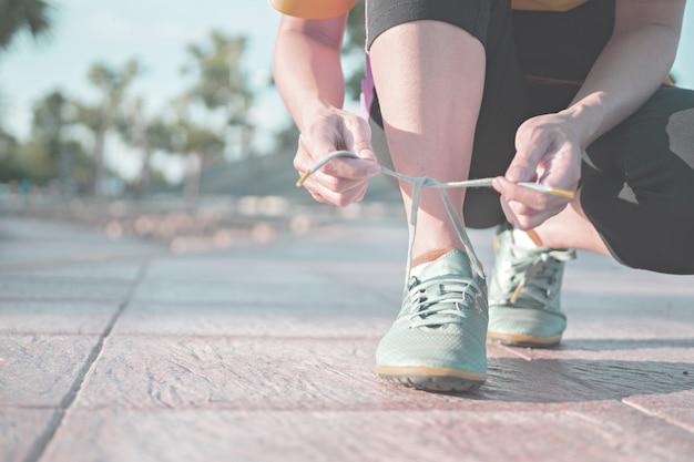 Laufschuhe - frau, die schnürsenkel bindet. nahaufnahme des weiblichen sporteignungsläufers, der zum draußen rütteln fertig wird. Premium Fotos