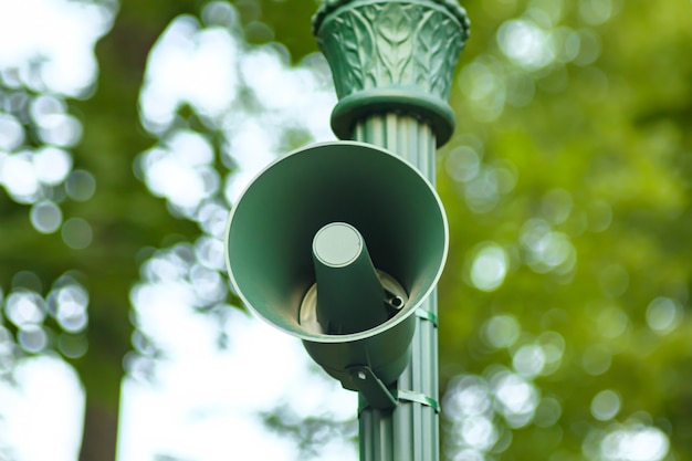 Lauter außenlautsprecher. public park audio-soundsystem. lautsprecher für sirene, alarm oder ansage. vintage grüne stimme sprechen megaphon auf säule für informationssendung, allert Premium Fotos