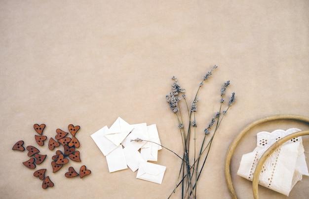 Lavendel, holzknöpfe, hausgemachte umschläge, alter holzrahmen und bänder mit saum auf kraftpapier. Premium Fotos