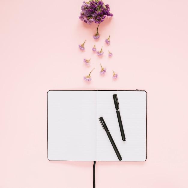 Lavendelblumen über dem geöffneten buch und zwei filzstifte auf farbigem hintergrund Kostenlose Fotos