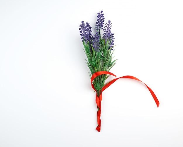 Lavendelblumenstrauß und rotes band auf einem weißen hintergrund, draufsicht Premium Fotos