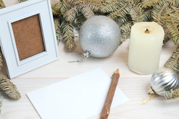 Layout eines fotorahmens, papiers, bleistifts auf einem weihnachtsthema auf einem weißen holztisch Premium Fotos