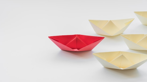Leader papierschiff gefolgt von weißen booten Kostenlose Fotos