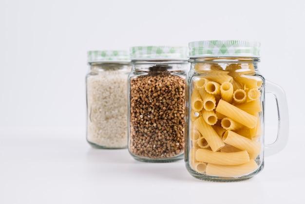 Lebensmittel in den gläsern auf weißem hintergrund Kostenlose Fotos