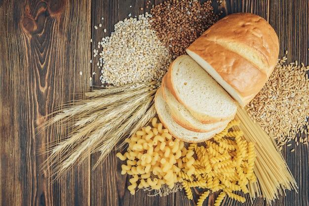 Lebensmittel mit hohem kohlenhydratgehalt auf hölzernem hintergrund. laib, nudeln, perlgerste und hafer. Premium Fotos