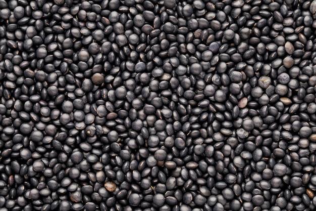 Lebensmittel- und kochhintergrund von gesunden getrockneten schwarzen linsen. Premium Fotos