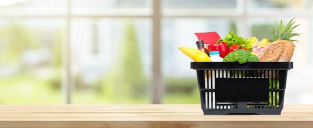 Lebensmittel und lebensmittelgeschäfte im einkaufskorb auf küchentischfahnenhintergrund Premium Fotos