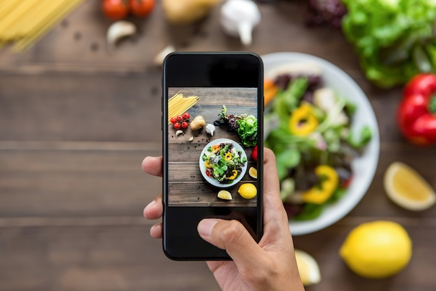Lebensmittelblogger unter verwendung des smartphone, der foto des schönen salats macht Premium Fotos