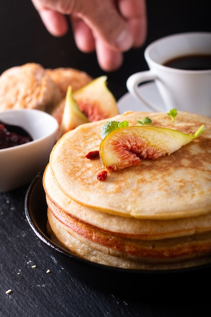 Lebensmittelkonzept selbst gemachter organischer pfannkuchenstapel mit feigenfrühstück auf schwarzem Premium Fotos