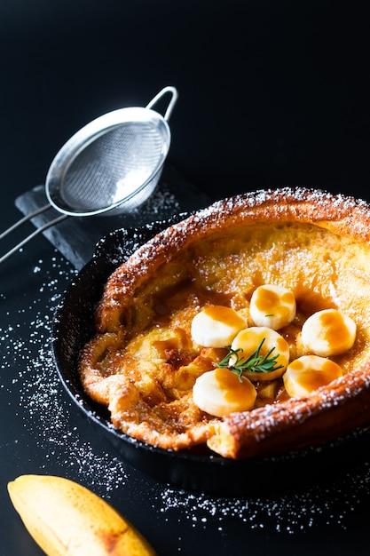 Lebensmittelkonzept selbst gemachtes niederländisches baby oder deutscher bananenkaramellbelagpfannkuchen im bratpfanneneisen warfen auf schwarzes Premium Fotos