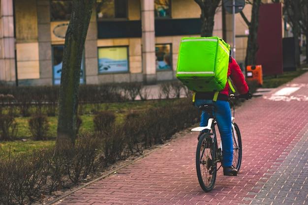 Lebensmittellieferungsfahrer mit grünem rucksack auf einem fahrrad, das entlang eine straße fährt Premium Fotos