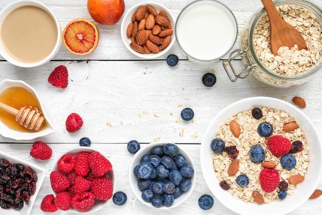 Lebensmittelrahmen aus frühstückszutat. müsli, obst, beeren, cappuccino, nony, milch und nüsse. gesundes essen Premium Fotos
