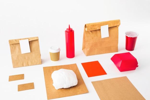 Lebensmittelverpackungen mit besetzungsschalen- und soßenflasche auf weißem hintergrund Kostenlose Fotos