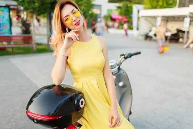 Lebensstil-außenporträt der stilvollen frau im gelben weinlesekleid sitzen auf schwarzem elektromotorrad. Kostenlose Fotos
