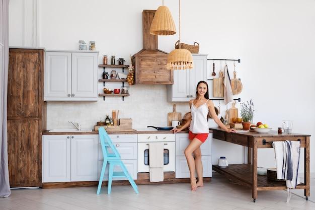 Lebensstil des netten mädchens den ofen in der küche bereitstehend, nette aromen vom braten des lebensmittels kochend und riechend Premium Fotos
